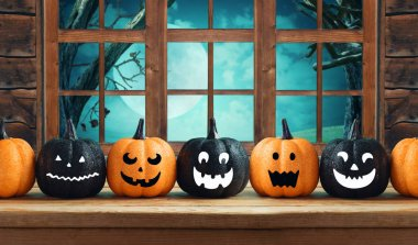 Halloween background with glitter pumpkin characters decor on wooden table over window and night landscape