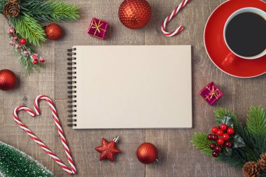 Christmas holiday background with notebook, coffee cup and decorations on wooden table. Top view from above