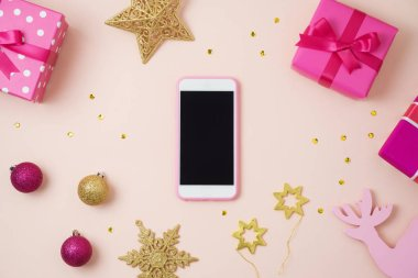 Christmas holiday smart phone mock up, pink gift boxes and decorations on table. Top view from above stock vector