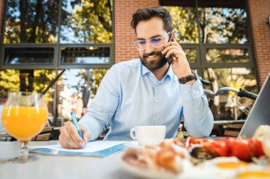 Happy young businessman talking on the phone and writing on paper while having breakfast at a restaurant.
