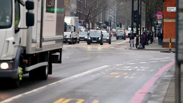 LONDON - MARCH 19, 2020: Busy rush hour traffic comes to a stop at traffic lights on London's Euston Road. Pedestrians cross the road and traffic from the opposite direction turns right.