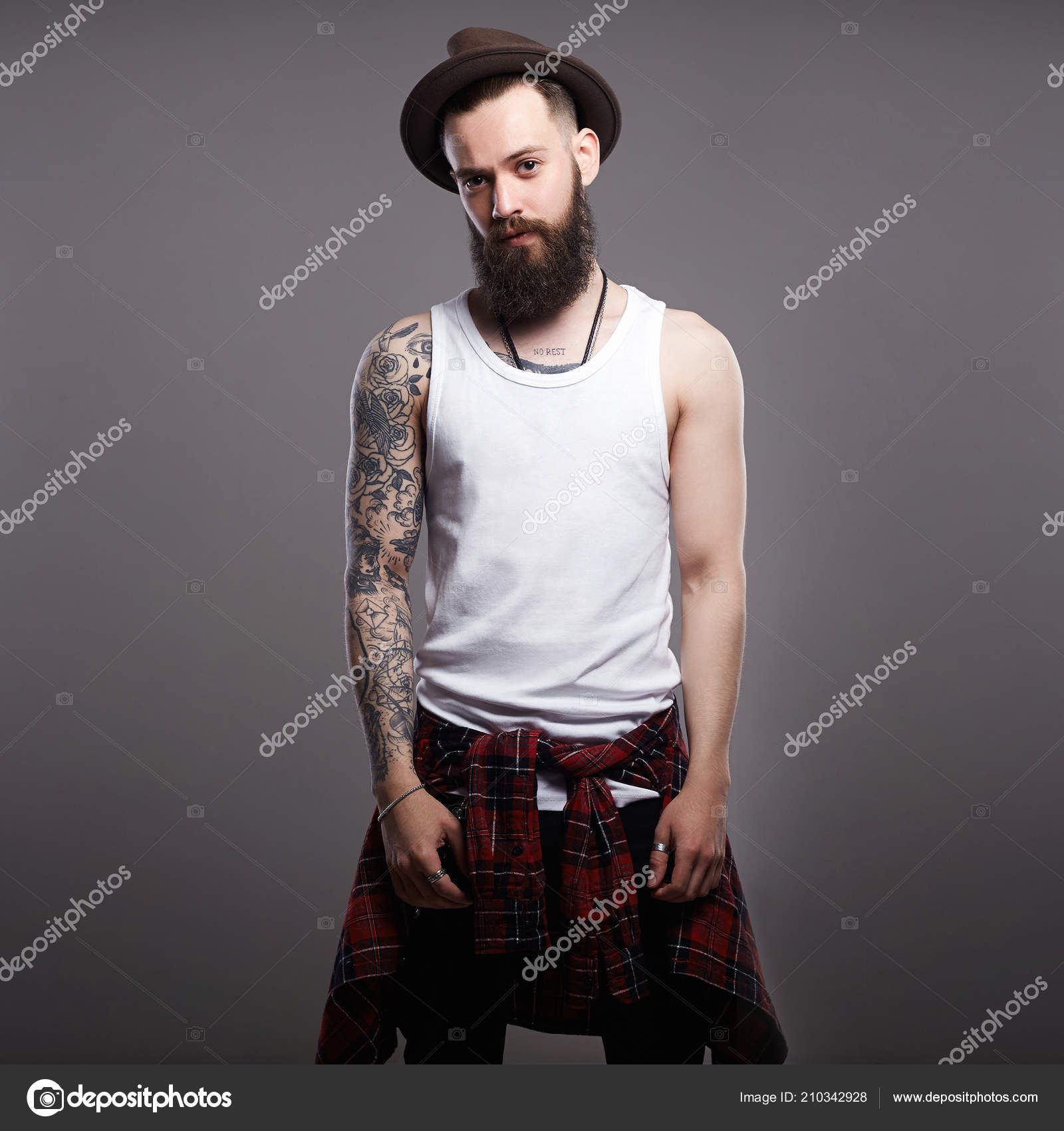 Retrato de hombre joven con barba de moda. Sonriente niño Hipster. hombre  guapo en el sombrero. Chico barba brutal con tatuaje — Foto de  EugenePartyzan b8aefdf2796