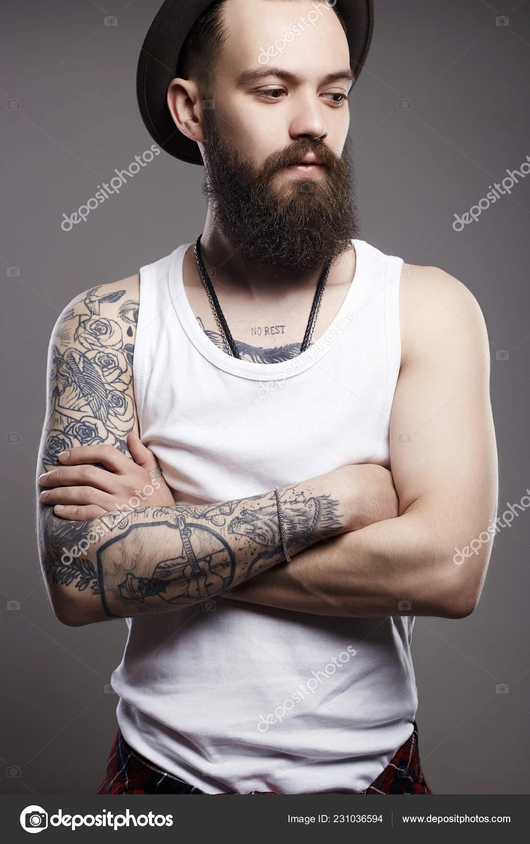 Retrato de hombre joven con barba de moda. Chico hipster. hombre guapo en  el sombrero. Chico barba brutal con tatuaje — Foto de EugenePartyzan 0a9eb096cf3