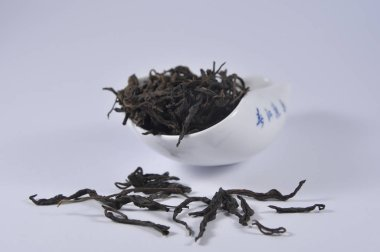 Chinese black tea in tea ware. Dry tea leaf. Product photo of Chinese tea. Tea and infusions. Heap of dry tea.