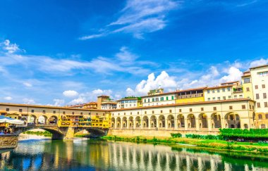 Ponte Vecchio bridge with colourful buildings houses over Arno River blue reflecting water and embankment promenade archways, historical centre of Florence city, blue sky white clouds, Tuscany, Italy