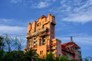 Orlando, Florida. March 19, 2019.The Twilight zone Tower of Terror and palm trees on lightblue cloudy sky background in Hollywood Studios at Walt Disney World