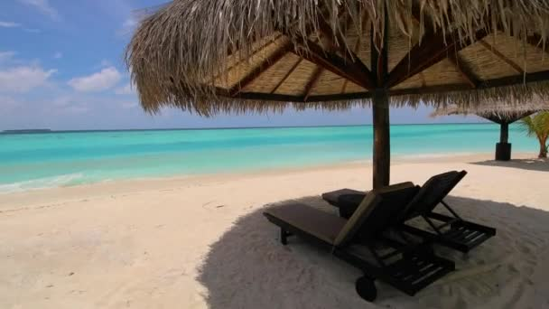 Under the parasol in Maldives. Amazing beach with parasols, deck chairs and shallow waters of local lagoon in Kihaad Maldives.