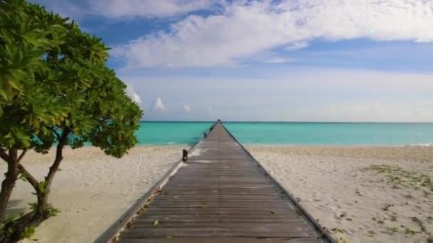 Písečná pláž v Maledivy, vlny, přístavních mol, azurově moře. Cesta k moři