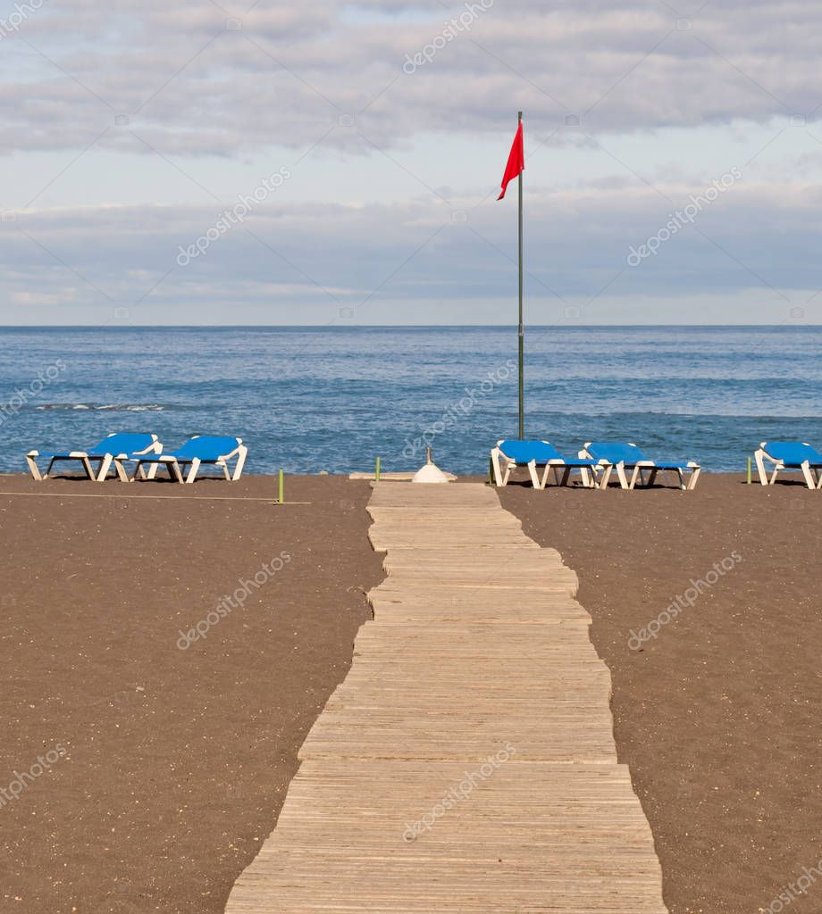 Boardwalk at the beach are several hammocks and a red flag, is located in Puerto de la Cruz in Tenerife