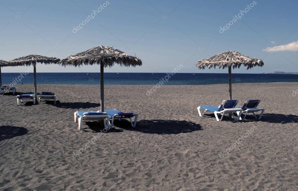 Several umbrellas and hammocks on the beach sand