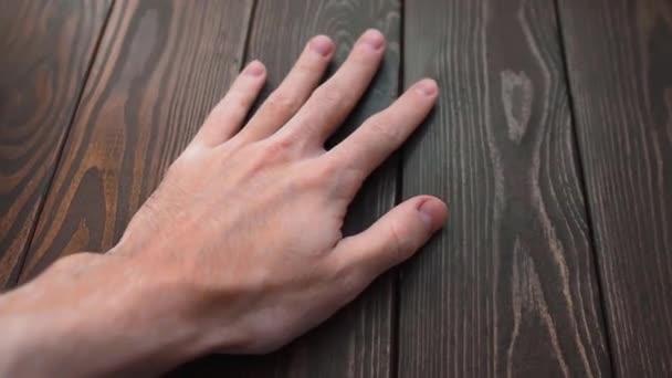 Hand streicht über eine schöne hochwertige braune Kiefernholz-Textur