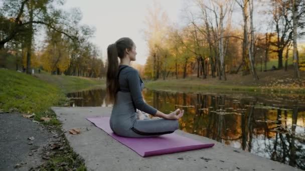 Mladá žena cvičí jógu venku. Žena meditovat venkovní infront krásná podzimní příroda.