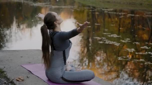 junge Frau praktiziert Yoga im Freien. Frauen meditieren im Freien vor der schönen herbstlichen Natur.