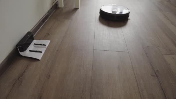 Ein Staubsaugerroboter gleitet durch ein modernes Wohnzimmer und zieht in die Ladefläche. 4k.
