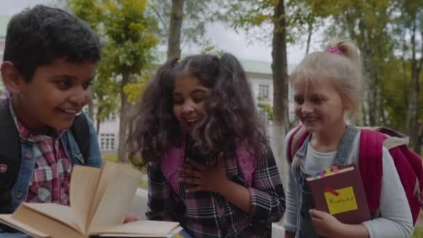 Vissza az iskolába. Közelről három barátok hátizsákok átölel, és nevetve az iskola előtt. Vegyes faji csoport iskola Kids szórakozik az iskolaudvaron. Lassított lövés.