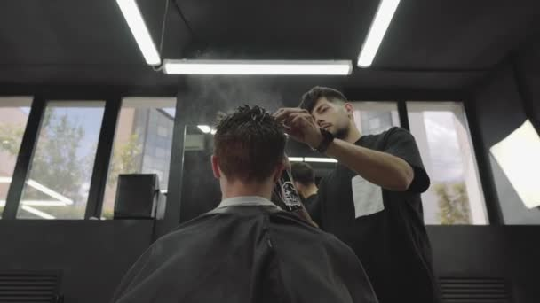 Barber wets hair by spray and combs them. Attractive male is getting a modern haircut in barber shop. Handheld shot. 4K.