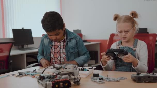 Smíšená rasová skupina dětí, kteří sedí na třídě s samoobslužném robotem, koncept pro vzdělávání kmenových škol.