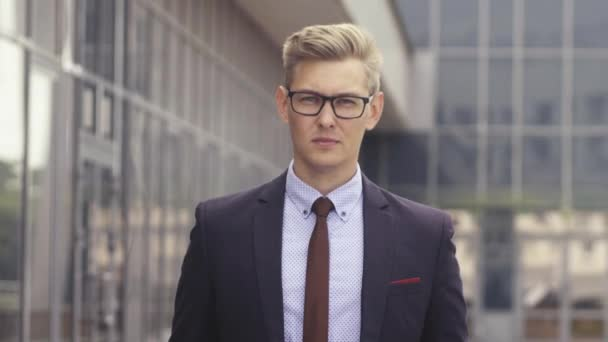 Portrait man in suit in front of office building. Handsome businessman outdoor. Male business person stands on street and looking away. Businessman dressed in formal clothes and glasses.
