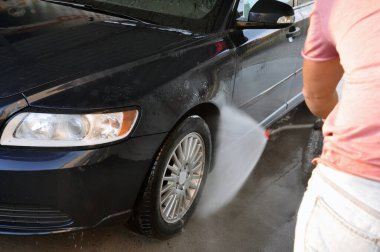 Summer car wash on a contactless self-service car wash. Cleaning a car using high pressure water.