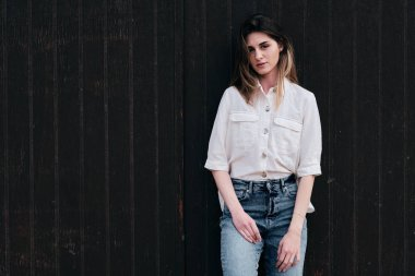 A young hipster beautiful woman with long brown hair in summer with denim jeans with a brown background