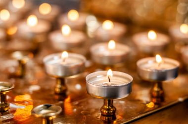 Burning candles on the golden stand