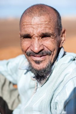 Portrait of old man who is resting on a dune erg chebbi at Merzouga, Morocco
