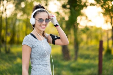 Young sexy sporty woman listening to music