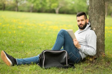 young man sitting on the grass and listening to music
