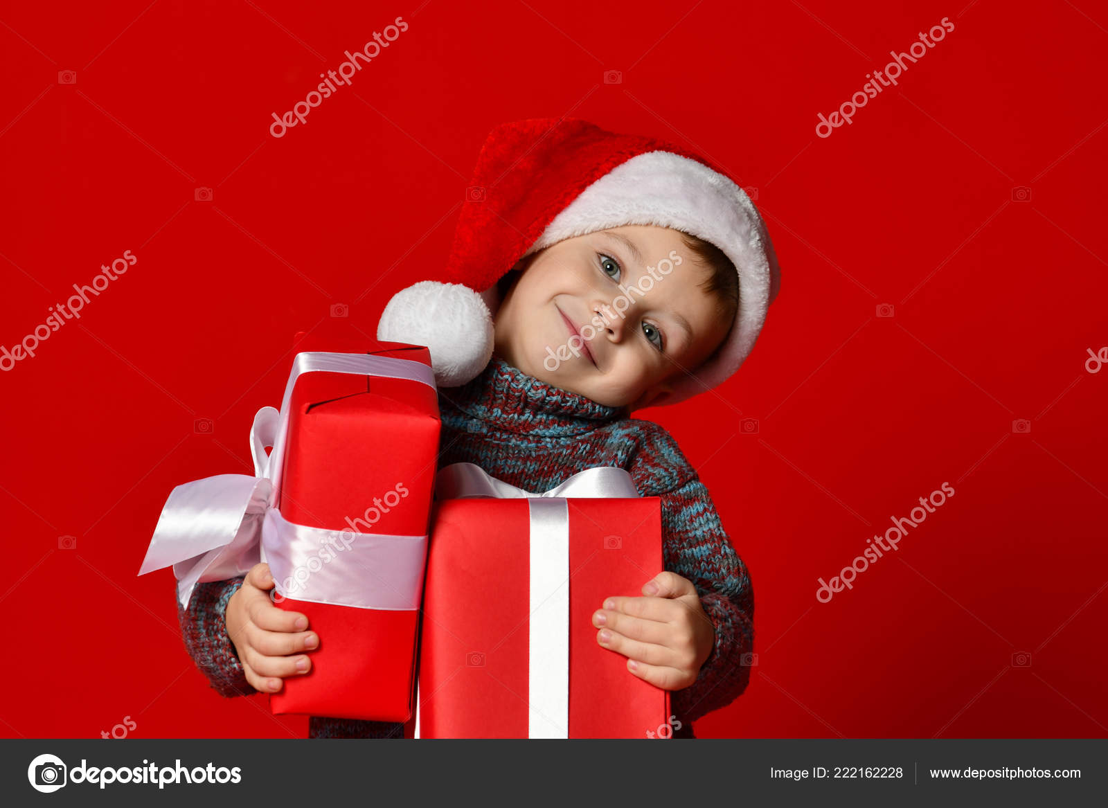 45ec4990d57b2 Funny smiling child in Santa red hat holding Christmas gift in hand. — Stock  Photo
