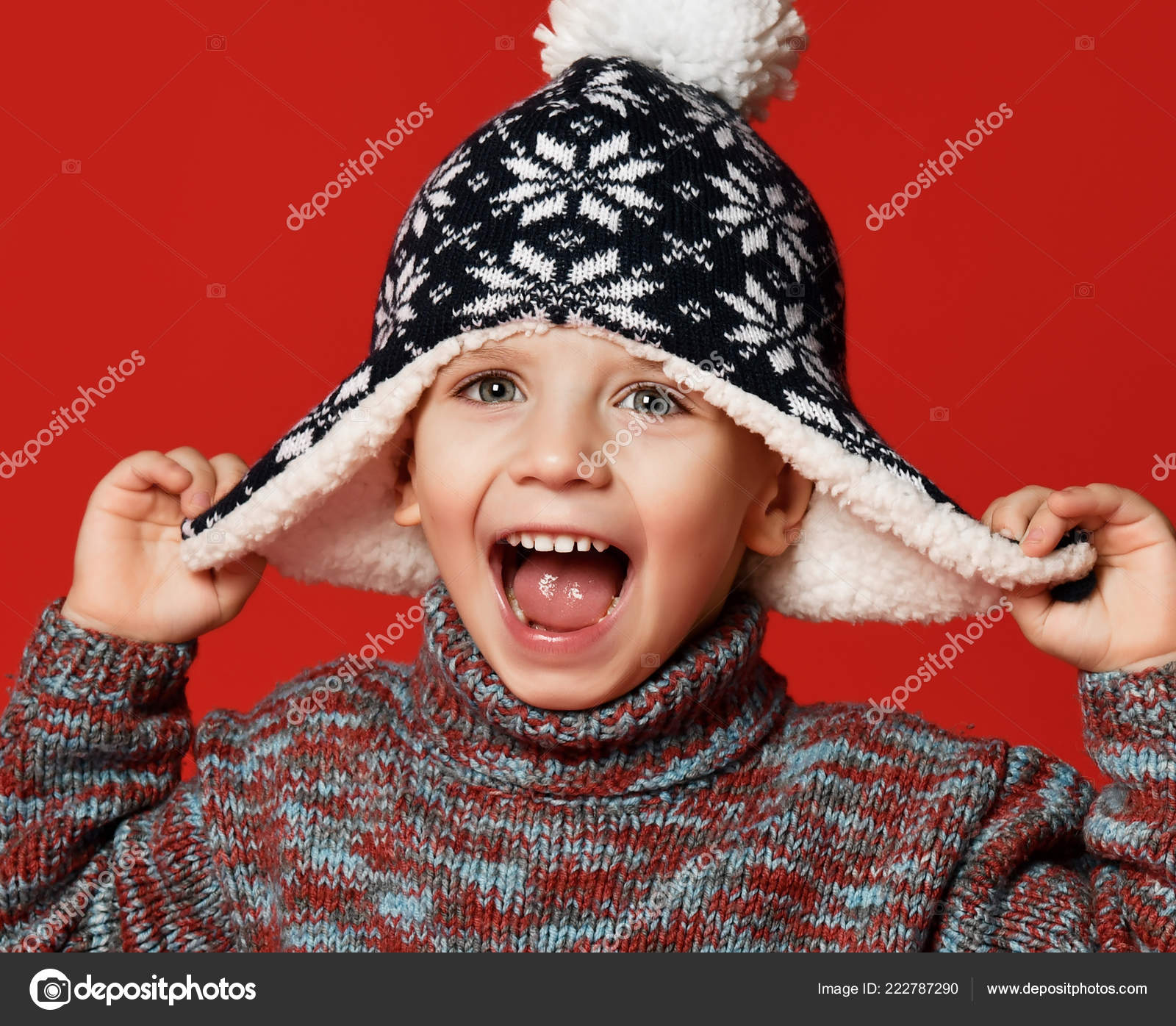 dc7c6ae90d8 Happy child boy toddler in knitted hat and sweater having fun screaming  laughing with open mouth close up winter composition over red background.