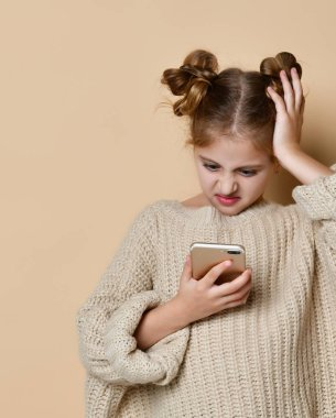 beautiful blond little girl looks at the phone confusedly, isolated studio photo on the background