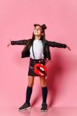 Kleines modisches Hipster-Punk-Mädchen in Lederjacke und Rock, schwarzen Kniehöhen, mit lustiger Frisur und Make-up-Star im Gesicht, die Arme freudig zur Seite gestreckt