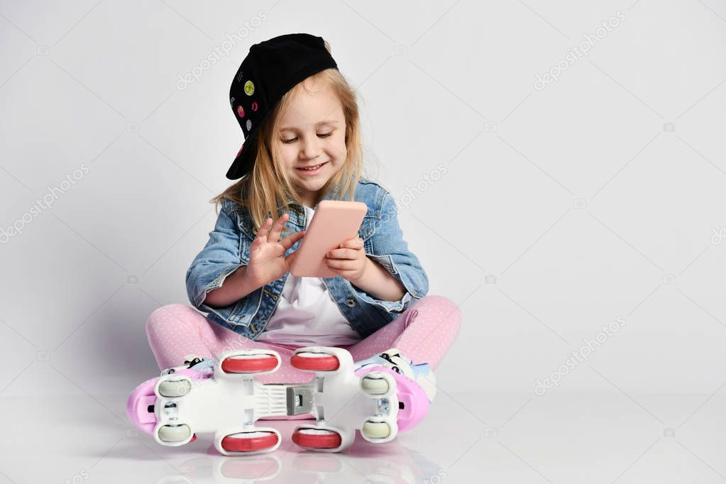 girl sits on the rollers in a blue denim and cap and smiles. Summer sports for children.