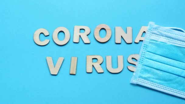 Word coronavirus disappears, the word summer appears. Medical mask saves from coronavirus. Wooden letters on a blue background. The end of the global pandemic and the beginning of summer. Stop motion.
