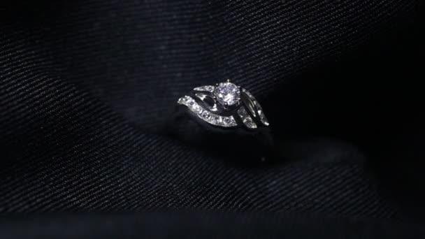 Extrémní detail diamantového prstenu zblízka na tmavém pozadí. Snubní prsten byl pořízen pomocí makro čočky s mělkou hloubkou pole. zásnubní, manželská a svatební koncepce