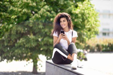 Modern Arab woman listening to music with earphones outdoors. North African girl in sportswear with curly hairstyle sitting in urban background.