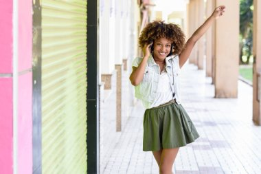Young attractive black woman in urban street listening to the music with headphones. Girl wearing casual clothes with afro hairstyle