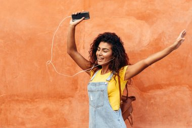 Happy Arab girl listening to music and dancing with earphones outdoors. African woman in casual clothes with curly hairstyle in urban background.