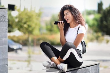 Beautiful African woman recording a voice note with smart phone outdoors. Arab girl in sport clothes with curly hairstyle in urban background.