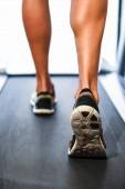 männliche muskulöse Beine, die auf dem Laufband im Fitnessstudio laufen. Konzept für Fitness, Bewegung und gesunden Lebensstil.