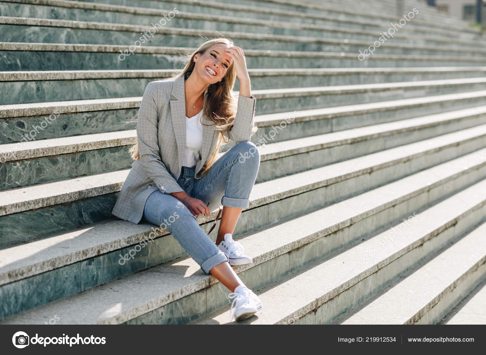 4a9fe6276 Hermosa mujer caucásica joven sonriendo en el fondo urbano. Chica rubia con ropa  casual en la calle. Mujer con chaqueta elegante y vaqueros sentados en ...