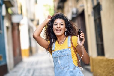 Attractive North African woman listening to music with earphones outdoors. Arab girl in casual clothes with curly hairstyle in urban background.