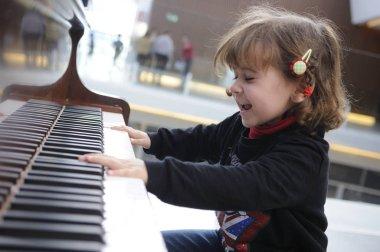 Adorable little girl having fun playing the piano