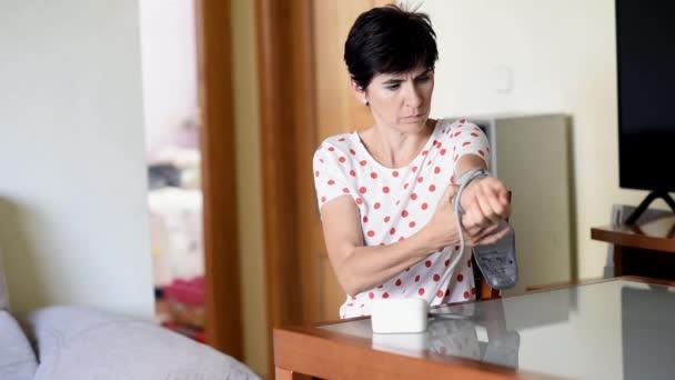 Frau mittleren Alters misst ihren eigenen Blutdruck mit einem elektronischen Blutdruckmessgerät.