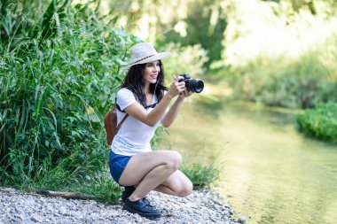 Beautiful hiker young woman taking photographs with a mirrorless camera, wearing straw hat, hiking in the countryside. stock vector