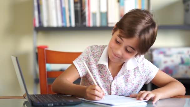 Kislány írás és rajzolás. Csinálás lecke-val laptop és jegyzetfüzet. Gyermek tanul otthon egy polc tele könyvek a háttérben.