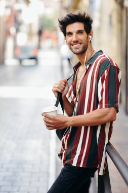 Young male traveler enjoying the streets of Granada, Spain. Man using earphones carrying backpack and a take-away glass. stock vector