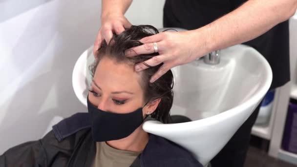 Friseurin wäscht einem Kunden in einem Salon den Kopf, geschützt durch eine Maske