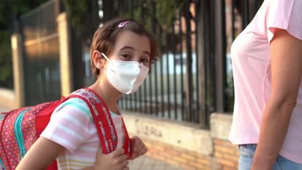 Kilenc éves lány táska sétált az anyjával kéz a kézben.