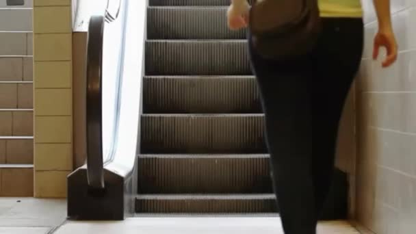 mladá dívka šlápne na eskalátoru a pohybuje se nahoru směrem ke světlu